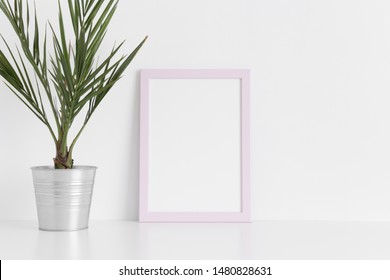 Pink frame mockup with a palm in a pot on a white table.Portrait orientation.