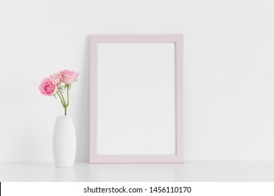 Pink frame mockup with pink roses in a vase on a white table.Portrait orientation.