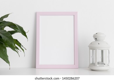 Pink frame mockup with a spathiphyllum and candle holder on a white table. Portrait orientation.