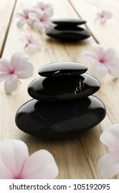 Pink frangipani flower and black stone, zen spa on wood
