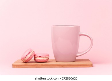 Pink french macaroons and pink cup of coffee lying on wooden board, on pink background