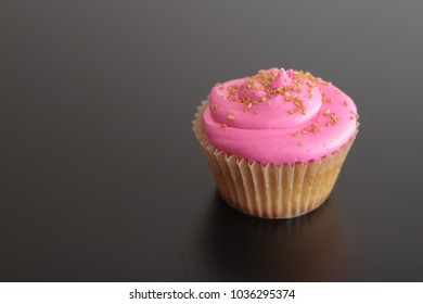 Pink Frosted Cupcake with Gold Sprinkles