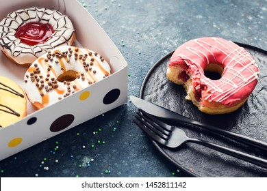 Pink frosted donut with bite missing on a plate with assortment donuts box on dark background. Top view. Copy space.