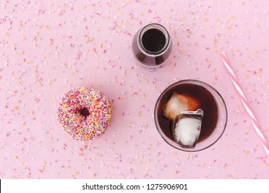 Pink frosted donut with colorful sprinkles, a glass filled with cold brew coffee, cold brew coffee concentrate in a milk bottle and a straw on pink background with multi colored sprinkles. Top view.
