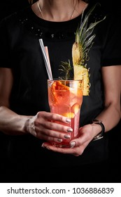 Pink fruit cocktail or lemonade in the hands of a woman in a black T-shirt.