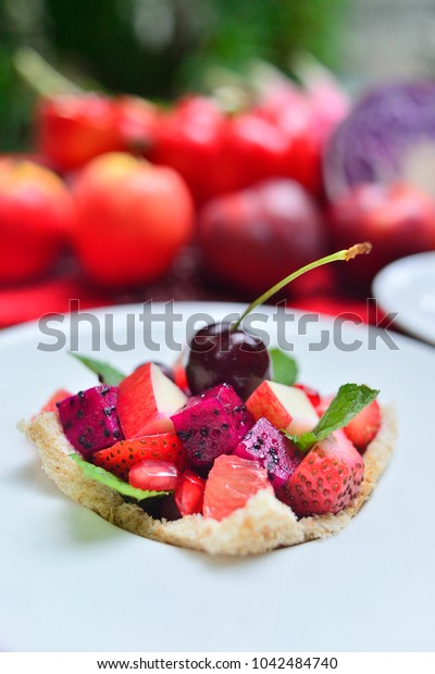 Pink fruit salad on bread slice and decorated with basil leaf in white plate,Assorted of various pink fruit put together.