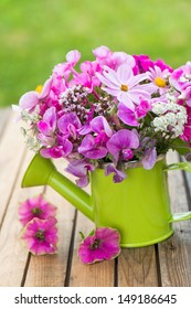 Pink garden flowers in a small watering can