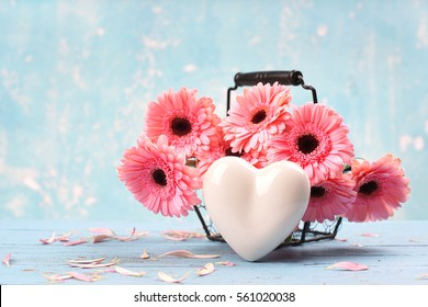 pink gerbera daisy in a basket and a White heart on blue wood, lovely background for Valentines Day, Birthday, Anniversary or floral greeting card.