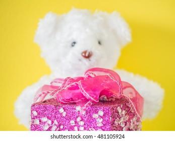 Pink gift box and blurry white bear toy with yellow wall.