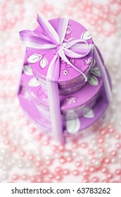 Pink gift box with a bow and beads