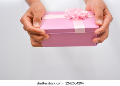 pink gift box in girl hands isolated on white background. can used for the holidays present.