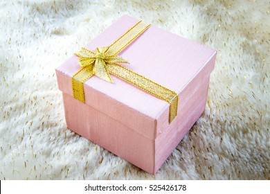 Pink gift box on fabric background