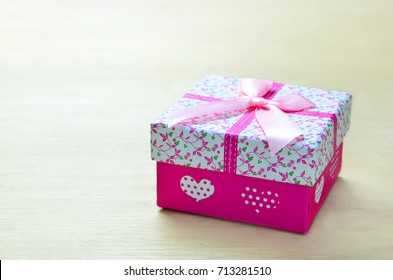 Pink gift box on wood background with copy space.