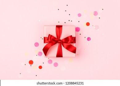 Pink gift box with red bow on pink background with sparkles. Holiday concept.