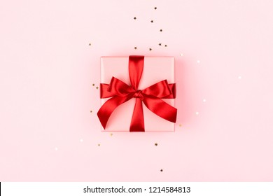 Pink gift box with red bow on the pink background with sparkles. Holiday concept.