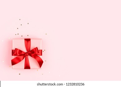 The pink gift box with red bow on the pink background with golden sparkles. Minimal styled holiday card with copy space.