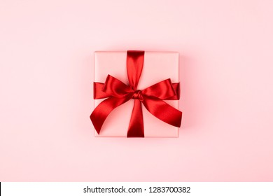 Pink gift box with red bow on the pink background. Valentine's day, 8 of March, Woman's day and birthday card.