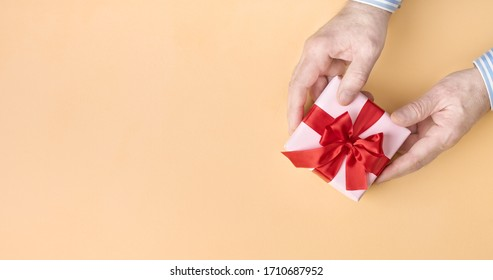 Pink gift box with red bow in male hands on pastel peach background. Directly above. Copy space