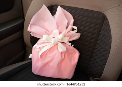 Pink Gift with a White Bow on a Car seat