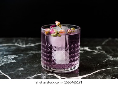 Pink Gin Tonic Cocktail with Dried Rose Buds, Purple Lavender and Ice in Glass Cup