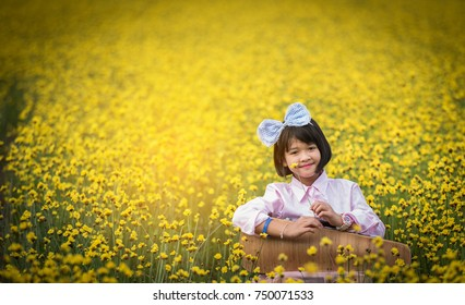 Pink girl In a field of yellow flowers.