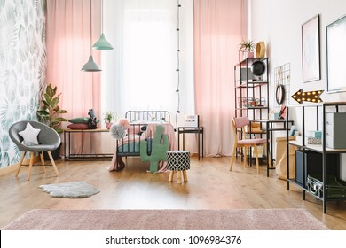 Pink girl room interior with a single bed, shelves, grey armchair and cactus shaped pillow
