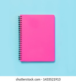 Pink girlish school supplies, notebooks on blue background. Top view, flat lay. Copy space.