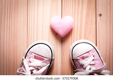 Pink girl's sneakers with pink hearts on a wooden floor, The concept of Valentine's Day.