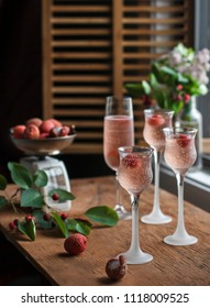 Pink glass of wine with litches and raspberries, vintage scale. Summer, splash of wine