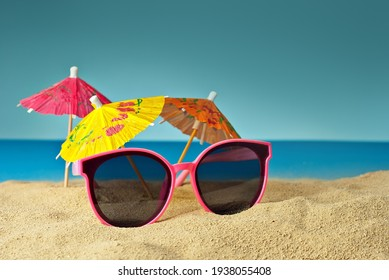 Pink glasses on the sand close up. Glasses on the beach on a background of paper umbrellas for cocktails. Summer, sea and vacation concept.