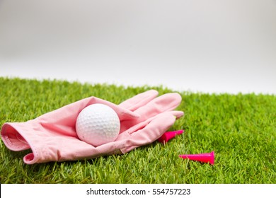 Pink glove and golf ball are on green course with pink tee for lady golfer.