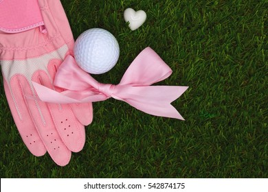 Pink glove with pink ribbon and golf ball with heart shape are on green grass, Idea for lady golfer.