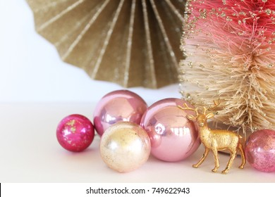 Pink and gold Christmas decorations with deer figurine. Copy space.