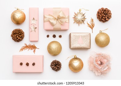Pink and gold christmas gifts isolated on white background. Wrapped xmas boxes, christmas ornaments, baubles and pine cones. Christmas composition.