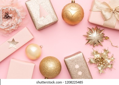 Pink and gold christmas gifts isolated on pastel pink background. Wrapped xmas boxes, christmas ornaments and baubles. Christmas mock up.