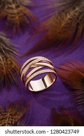 Pink gold fashion ring with diamonds on purple background with feathers. Jewellery advertising