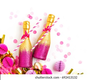 Pink and Gold Mini individual bottles for toasting of champagne with golden confetti and tinsel. Flat lay.  Holiday concept