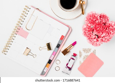 Pink and gold office details with electronics and desk accessories in a white background