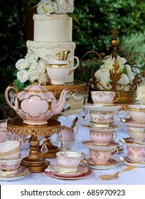 Pink and gold vintage high tea party, teacups, teapot, cake stands, wedding cake and crown.