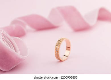 Pink gold wedding ring with diamonds and wave pattern on pink background with ribbon. Product concept for jeweler