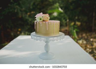 Pink and golden dripping cake with roses