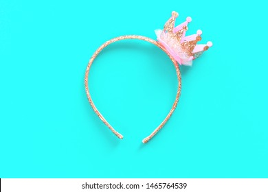 Pink and golden glitter princess crown headband for girls on blue background. Festive girlie feminine birthday party or performance. Flat lay minimalistic with copy space