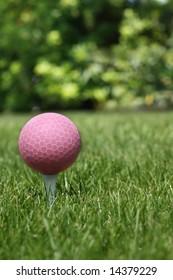 Pink golf ball on a tee.