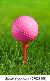 pink golf ball on a tee over green grass outdoors