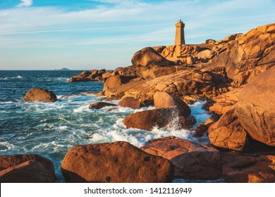 Pink Granite Coast in Brittany near Ploumanach, France.Ploumanach Mean Ruz lighthouse red sunset in pink granite coast, Perros Guirec, Brittany