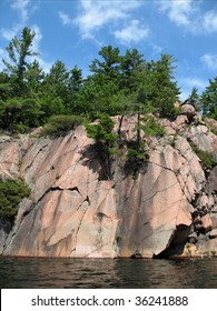 Pink granite rock with pine trees along the shore of a pristine lake in Northern Ontario, Killarney.