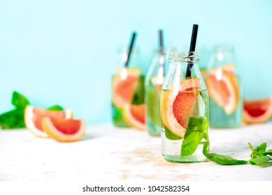 Pink grapefruit and fresh basil infused drink  in bottles, spa fruit water, or summer party alcoholic jin tonic cocktail served in small shots, front view, space for a text