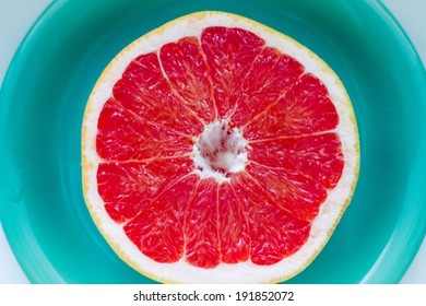 A pink grapefruit isolated on the plate