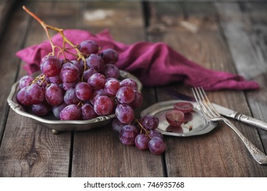 Pink grapes in plate on wooden table