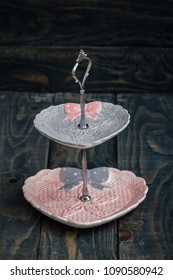 Pink and gray colored tier serving trays on blue background